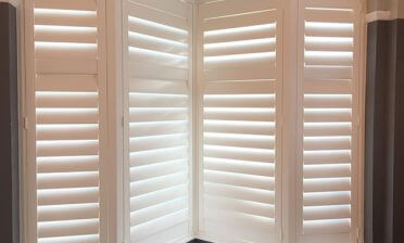 White Teak Shutters installed to angled bay window in South Croydon